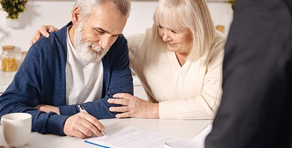 Elderly Couple Signing Paperwork
